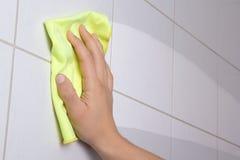 Mano con el trapo amarillo que limpia las tejas del cuarto de baño Foto de archivo