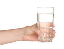 Mano con el vidrio de agua Fotos de archivo libres de regalías
