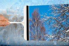 Mano con el vidrio de la ventana de limpieza del raspador Imagenes de archivo