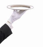 Mano con guantes de los mayordomos con la bandeja Imagen de archivo