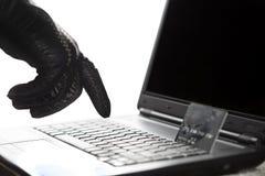 Mano con guantes de los piratas informáticos en el trabajo sobre un ordenador portátil Imagenes de archivo