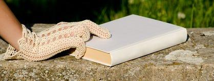 Mano con guantes del cordón en el libro blanco fotos de archivo