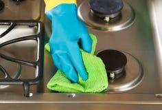 Mano con guantes que limpia abajo de gama del top de la estufa con ra verde de la microfibra Fotos de archivo libres de regalías