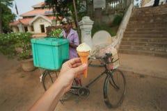 Mano con helado dulce en la calle y el comerciante de postres en ciclo Fotos de archivo libres de regalías