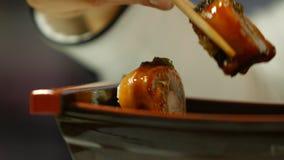 Mano con i bastoncini che prendono i sushi stock footage