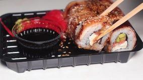 Mano con i bastoncini che prendono i sushi Il sushi arriva a fiumi un recipiente di plastica scuro Movimento lento archivi video