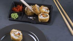 Mano con i bastoncini che prendono i sushi Rotoli di sushi sul piatto scuro tempo dello spuntino del ` s archivi video