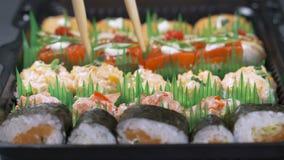 Mano con i bastoncini che prendono i sushi Rotoli di sushi sul piatto scuro tempo dello spuntino del ` s video d archivio