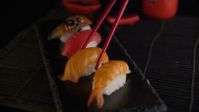Mano con i bastoncini rossi che prendono i sushi archivi video