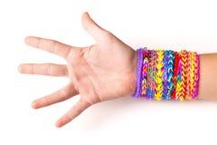 Mano con i braccialetti di gomma variopinti del telaio dell'arcobaleno su bianco fotografia stock libera da diritti
