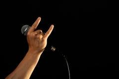Mano con i corni del diavolo e del microfono isolati sul nero Fotografia Stock