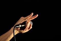 Mano con i corni del diavolo e del microfono isolati sul nero Immagini Stock