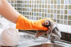 Mano con i guanti che puliscono il lavandino dell'acciaio inossidabile con il panno Fotografie Stock Libere da Diritti