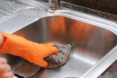 Mano con i guanti che puliscono il lavandino dell'acciaio inossidabile con il panno Fotografia Stock Libera da Diritti