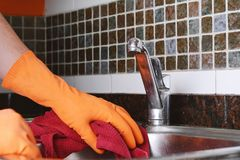 Mano con i guanti che puliscono il lavandino dell'acciaio inossidabile con il panno Immagine Stock
