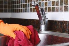 Mano con i guanti che puliscono il lavandino dell'acciaio inossidabile con il panno Immagine Stock Libera da Diritti