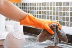 Mano con i guanti che puliscono il lavandino dell'acciaio inossidabile con il panno Immagini Stock Libere da Diritti