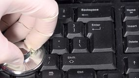 Mano con i guanti e stetoscopio sulla vecchia tastiera Concetto di sistemi diagnostici del computer archivi video
