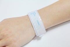 Mano con il braccialetto paziente dell'identificazione Immagini Stock Libere da Diritti