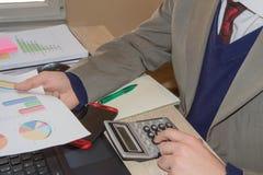 Mano con il calcolatore Affare di contabilità e di finanza Uomo d'affari Calculating Finance Bills in ufficio Penna sui conti di  Immagine Stock Libera da Diritti