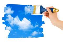 Mano con il cielo della pittura del pennello Fotografia Stock