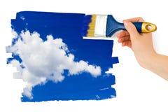 Mano con il cielo della pittura del pennello Immagine Stock