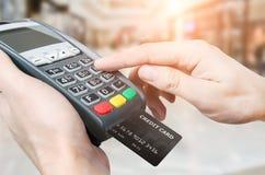 Mano con il colpo della carta di credito tramite il terminale da vendere in superma Fotografia Stock