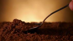 Mano con il cucchiaio che spinge attraverso il cacao in polvere - la macchina fotografica segue archivi video