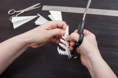 Mano con il fiocco di neve del taglio di forbici da carta Fotografia Stock Libera da Diritti