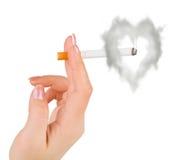 Mano con il fumo a forma di del cuore e della sigaretta Immagine Stock