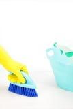 Mano con il guanto facendo uso della spazzola di pulizia per pulire il pavimento Immagine Stock
