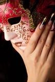 Mano con il manicure che tiene mascherina veneziana Fotografie Stock Libere da Diritti