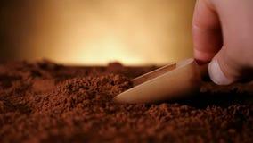 Mano con il mestolo di legno che spinge attraverso il cacao in polvere stock footage