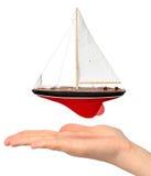 Mano con il modello dell'yacht Fotografia Stock