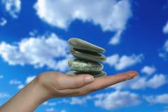 Mano con il mucchio delle pietre di zen Fotografie Stock Libere da Diritti