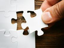 Mano con il pezzo mancante del puzzle Immagine di concetto di affari per il completamento del pezzo finale di puzzle Immagini Stock