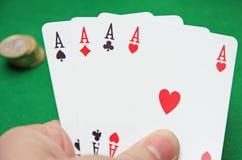 Mano con il poker degli assi su un gioco di tabella verde Immagini Stock Libere da Diritti