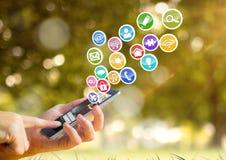 mano con il telefono con le icone dell'applicazione che vengono su da  Fondo verde del boke Immagini Stock