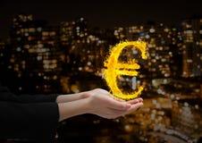 mano con l'euro icona del fuoco più davanti alla città vaga alla notte Fotografia Stock Libera da Diritti