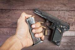 Mano con la bala y arma semiautomático de 9m m en fondo de madera Imagen de archivo libre de regalías