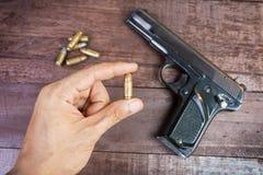Mano con la bala y arma semiautomático de 9m m en fondo de madera Foto de archivo libre de regalías