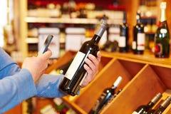 Mano con la bottiglia di vino di esame dello smartphone Fotografia Stock