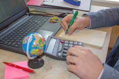 Mano con la calculadora Negocio de las finanzas y de la contabilidad Hombre de negocios joven Calculating Finance Bills en oficin Imágenes de archivo libres de regalías