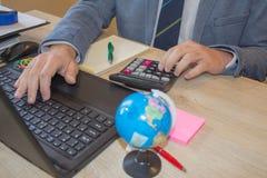 Mano con la calculadora Negocio de las finanzas y de la contabilidad Hombre de negocios joven Calculating Finance Bills en oficin Imagen de archivo libre de regalías