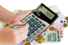 Mano con la calculadora y el dinero imagenes de archivo