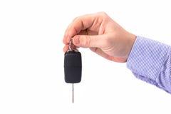 Mano con la chiave dell'automobile sopra bianco Fotografia Stock