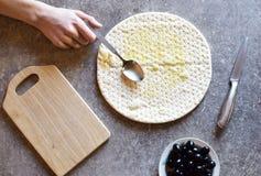 Mano con la cuchara que añade el aceite de oliva en la pasta de la pizza Fotos de archivo
