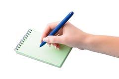Mano con la escritura de la pluma en el cuaderno Fotografía de archivo