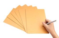 Mano con la escritura de la pluma en el sobre en el fondo blanco Fotos de archivo
