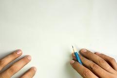 Mano con la escritura del lápiz en el fondo blanco, espacio libre foto de archivo libre de regalías
